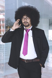 African american businessman with afro hair talking on the phone - 195875664