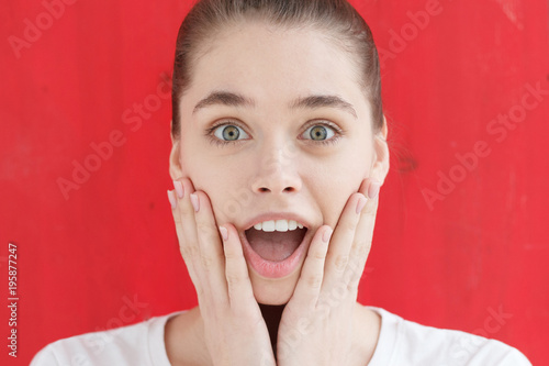 Are you kidding me? Oh my god! Wow! Really? Crazy shocked young girl, looking at camera with wide opened mouth and bugged eyes, standing against bright red background
