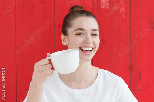 1ce267e208b Portrait of young woman in white tshirt with big coffee cup in hand,  smiling widely
