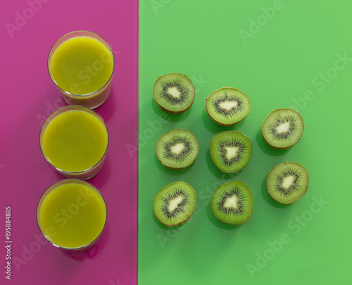 Foto op Canvas Sap kiwi juice and kiwi fruit on green-purple glass background.