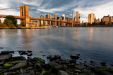Brooklyn Bridge and rocky shore with the New York skyline