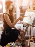Artist painting on easel and palette in studio. Authentic girl paints with oil brush in morning sunlight dawn light toning window background. Flowers with watercolor. Sun flare and drawing homework. - 195888623