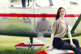 young woman in front of prop plane getting ready to travel
