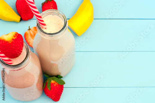Keuken foto achterwand Milkshake Fresh strawberry and banana milkshake on a turquoise wooden background (copy space)