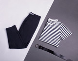 Simple casual monochrome b&w outfit with striped t-shirt, black cigarette trousers and black belt isolated on gray and white background. Flat lay. Copy space.