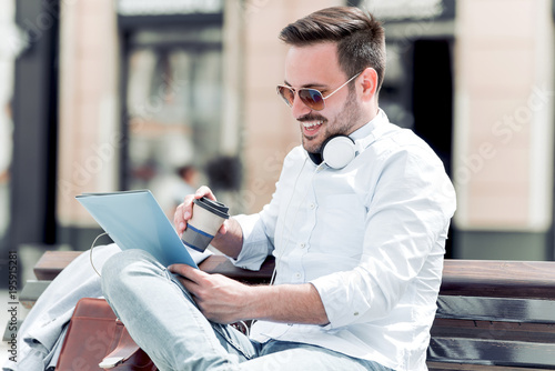 Young businessman sitting on the bench with coffee to go