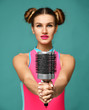happy fashion brunette woman singing with big hair comb brush on modern blue mint
