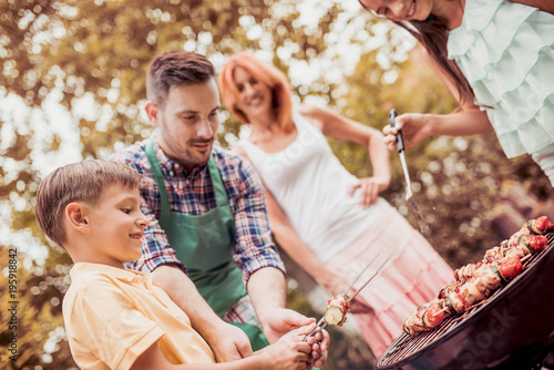 Family having a barbecue party,standing around the grill