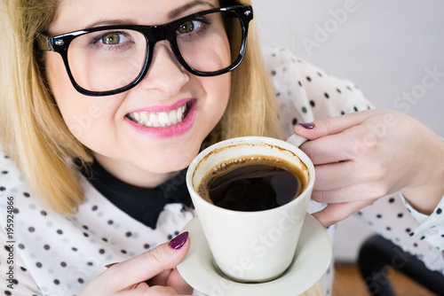 Poster Happy woman at office drinking hot coffee