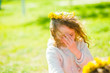 The girl in a wreath of dandelions covered her face with her hand. Child on a walk in the spring. The first rays of the sun. The first green grass.