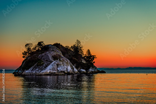 Foto op Canvas Canada rocky island with black silhouettes of trees and fir trees in the ocean
