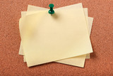 Several untidy yellow sticky post notes pinned to cork board - 195930880