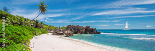 Sailing boat in the turquoise sea and sandy beach with palm trees and beautiful rocks on Seychelles. - 195958653