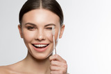 Portrait of excited young woman holding a toothbrush near her eye and laugh. Beauty and hygiene concept. Isolated and copy space - 195960488