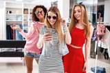 Pretty girls wearing sunglasses fooling around taking selfie showing tongue and horn gestures in clothing shop - 195966676