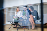 Caucasian business people meeting in boardroom behind glass - 195967220