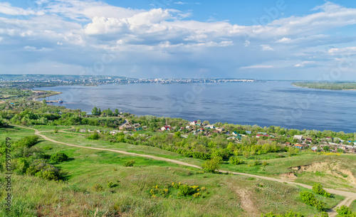 Keuken foto achterwand Pistache shore of the Volga River in summer, suburban houses, trees and green vegetation, with urban buildings in the background, against the blue sky and clouds