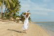 back view of slim girl in white dress walking on tropical beach with palms