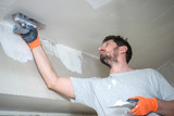 Worker Plastering Ceiling - 195980032