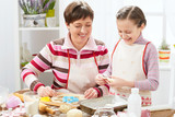 Mother and daughter cooking at home, making the dough for buns - 195982223