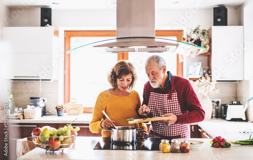 Senior couple preparing food in the kitchen. - 195982825