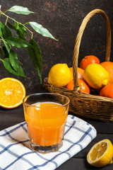 Orange juice in a glass beaker and basket with assortment of citrus fruits on a dark wooden background in rustic style