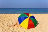 Elegant women's legs look out from under the colorful umbrella. - 195987015