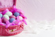 Pink basket full of colored Easter eggs and feathers on pink and white background