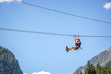 Teenager having fun on a zip line in the Alps, adventure, climbing, via ferrata during active vacations in summer - 195988628