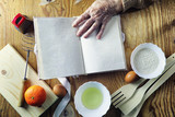 Open recipe book in the hands of an elderly woman - 196005474