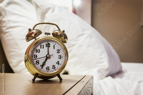 alarm clock stands on a bedside table in the room or hotel room - 196012253
