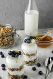 Homemade granola in a glass jar with yogurt and blueberries on a gray concrete background with a bottle of milk and honey. Food photography of a healthy morning breakfast. - 196016853