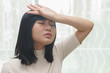Woman with headache or cold in her room - health concept.