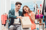 Woman showing her man in shopping bag what she bought in fashion store - 196029438