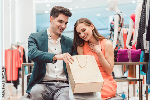 Foto op Plexiglas Hoogte schaal Woman showing her man in shopping bag what she bought in fashion store