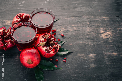Fresh pomegranate juice. Pomegranate. On a black wooden background. Top view. Copy space. - 196032493