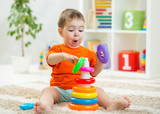 Baby toddler makes funny faces playing with educational toy on floor - 196034864