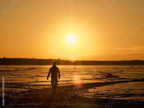 Fotobehang Strand A man walking toward the sunset on the frozen sea, Espoo, Finland
