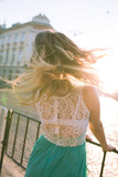 Romantic blonde girl with fluttering hair posing in sun rays in the morning