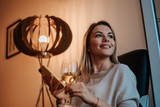 Close-up image of smiling woman enjoying glass of white wine at evening. Using smartphone. - 196049003