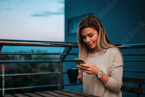 Poster Image of smiling woman using smartphone while drinking tea or coffee on teracce.