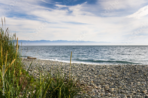 Foto op Canvas Canada Empty Stretch of a Pebble Beach along the Coast of Vancouver Island on a Partly Cloudy Summer Day