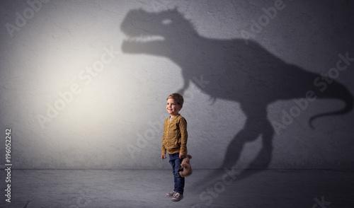 Fototapeta Dinosaurus shadow behind cute boy