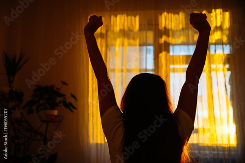 Papiers peints Morning Glory woman silhouette in front of window. sunrise in window. Wake up in morning