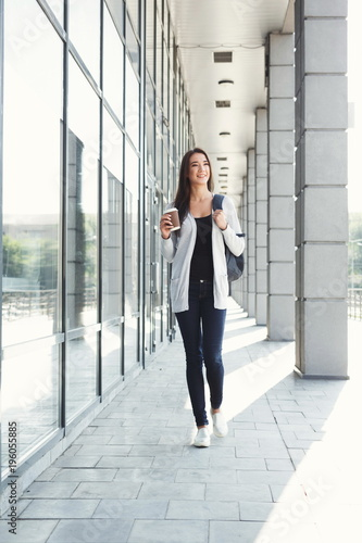 Beautiful student girl with backpack and coffee