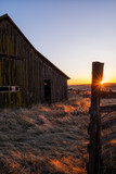 The sun sets on an old barn and fence - 196056274