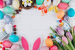 Easter composition with colored eggs, rabbit ears, candy, nest and tulips on a white wooden background.