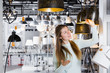 Girl buying plummed lamp in the modern furniture store
