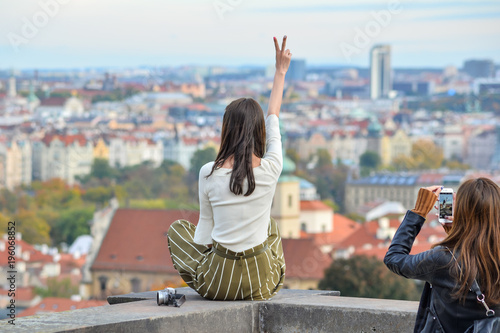 Staande foto Praag Prague, Czech Republic - October 10, 2017: Pretty Asian girl poses and looks at the old city of Prague from observation decks near Prague Castle, Prague, Czech Republic