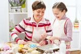 Mother and daughter cooking at home, making the dough for buns - 196071655
